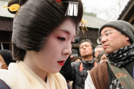 A maiko wades through the crowds before her performance.
