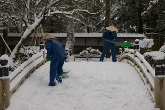 Staff hurriedly clear the snow from a bridge.