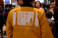 A man wears a special a happi coat announcing the start of the Hokuriku Shinkansen