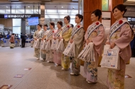 Ladies wearing hand painted, locally produced Kagayuzen kimonos prepare to distribute commemorative packs to the shinkansen passengers as they arrive from Tokyo