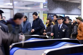 A station attendant manning the new ticket gates in a sea of travellers