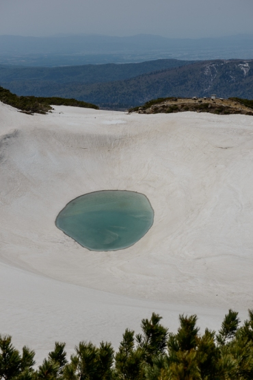 One of the small crater lakes begins to defrost on Asahidake, a volcano in Daisetsuzan National Park.