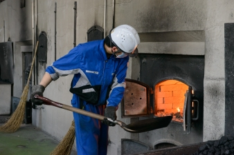 Adding coal to the roasting ovens in the stillhouse, Nikka Distillery, Hokkaido, Japan.