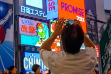 A tourist photographing the Glico Man, Shinsaibashi, Osaka.